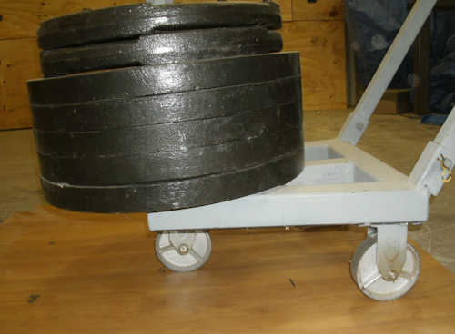 barbell plates stacked on top of a rolling load testing device